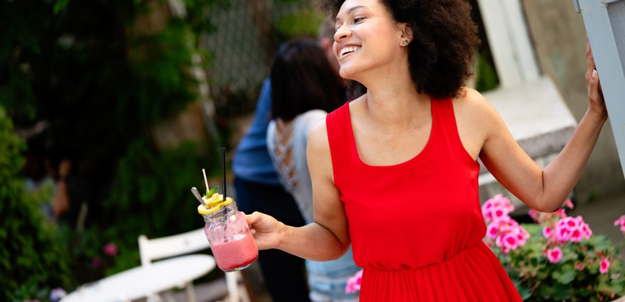 Beautiful happy black woman drinking healthy drink and smiling